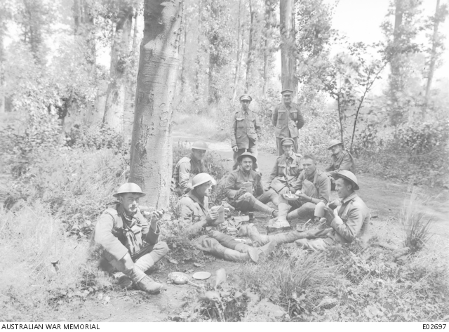 English, American and Australian troops lunching in a wood near Corbie, 3 July 1918.