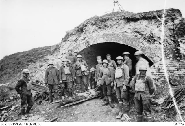 American stretcher-bearers and Australians of the 60th Battalion, AIF, with German prisoners, at one of the access entrances to the St. Quentin Canal at Bellicourt, 1 October 1918.