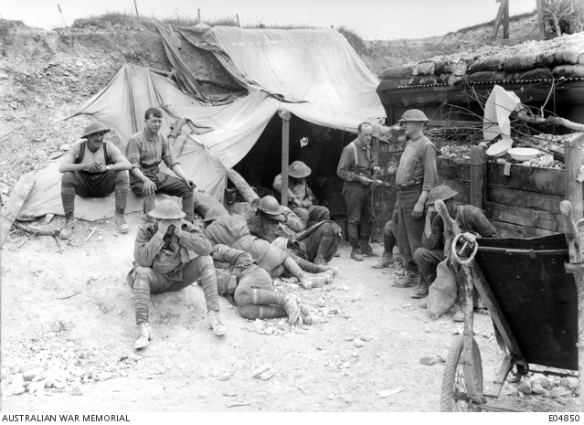A group of unidentified Australian soldiers, suffering from the effects of gas, gathered at the Regimental Aid Post of the 42nd Battalion awaiting medical attention.