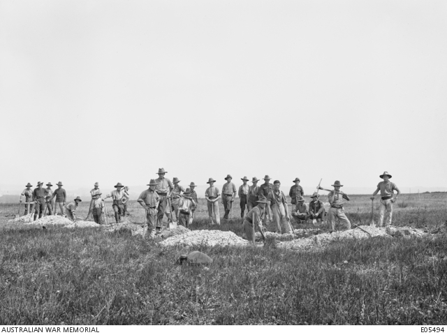 Unidentified members of No 5 Company of the Australian War Graves Detachment at work digging graves at the Villers-Bretonneux cemetery.