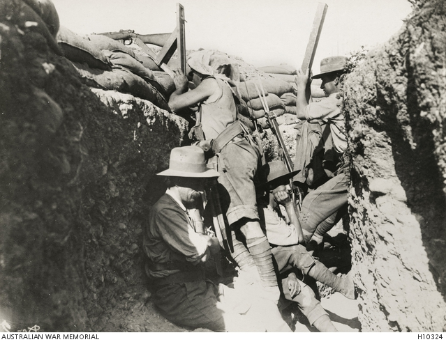 A sniper using a rifle with a periscopic sight while an observer checks the results with a trench periscope