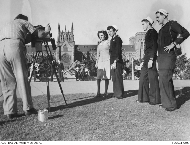 A member of the US Navy and his Australian woman companion pose for the while-you-wait photographer in Hyde Park with St Mary's Cathedral in the background.