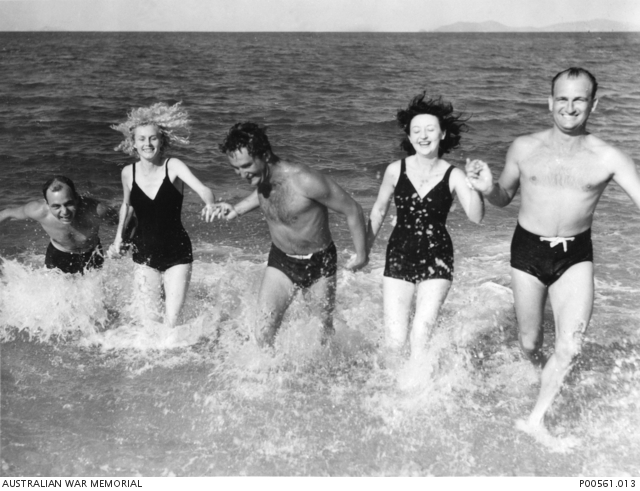 American servicemen splash in the sea at Eineo Beach with Air Force Victorettes,. P00561.013.