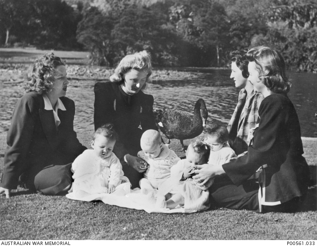 Melbourne, Vic. C. 1945. Four wives of American servicemen gather with their children in the Botanical Gardens. P00561.033.