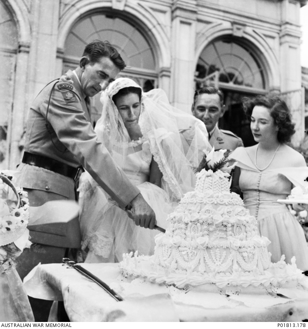 Lieutenant Colonel Fergus MacAdie (left), Commanding Officer of the 67th Infantry Battalion serving with BCOF, uses a ceremonial sword to cut the wedding cake at his wedding reception party at Mudge Hall. P01813.178.