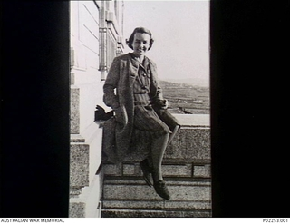 Informal portrait of the artist Sheila Hawkins (later Bowden), sitting on a stone wall at the entrance of the National Library of Wales at Aberystwyth, to which RAF squadron records were sent. ..