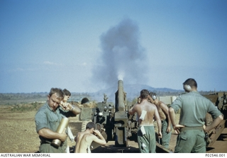 Members of 105th Field Battery firing an American M2A2 artillery piece. In the foreground, blocking his ear from the noise of the shell exploding, is 2787681 Ivan Parkes, 12th Field Regiment, of ..