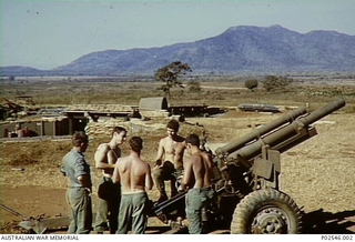 Members of 105th Field Battery gathered around an American M2A2 artillery piece. Second from the left with charge bags over his shoulder is Ian Smith from WA. The buildings in the background are ..