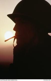 An informal portrait of 2786496 Gunner Steven Blake 12th Field Regiment, of Sydney, NSW, smoking a cigarette, silhouetted against the setting sun