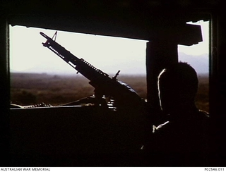 Informal portrait of 4179441 Gunner Stephen Lewis of 12th Field Regiment in a bunker on guard duty. During January and February 1969 guard duty was performed on a 24 hour basis, due to a fear of a ..