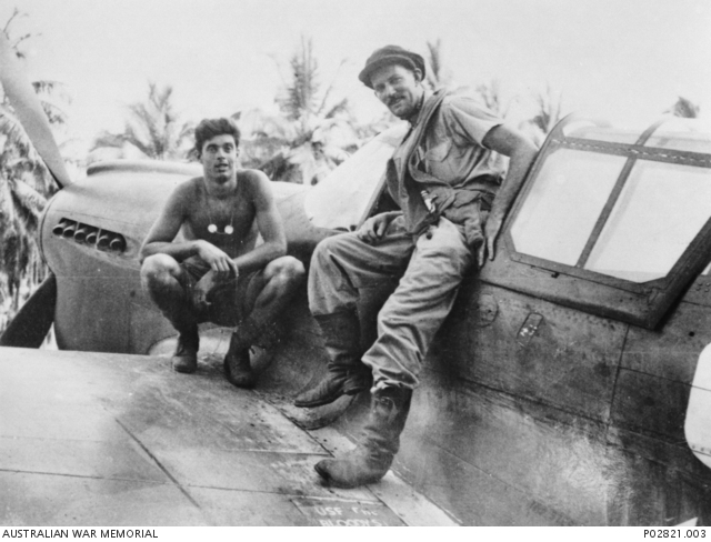 Flt Lt Brown sitting on the cockpit sill of his P-40 Kittyhawk aircraft 'Polly'.