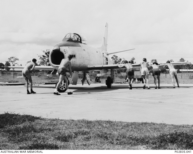 Unidentified Members Of A RAAF Squadron Probably 79 Pushing An Avon Sabre Aircraft