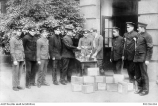 Distributing Red Cross parcels to allied Prisoners Of War (POW) at Kriegsgefstammlager (camp) at Limburg am Lahn, Germany. Identified, on the far left is 3890 Private (Pte) Benjamin (Ben) Ross, ..