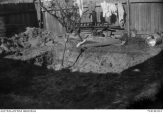A hole in the garden ready for an Anderson air raid shelter. The shelter is in the back yard of the Adams family home at 405 Gardeners Road, Mascot, Sydney