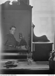 Self portrait of 18 Gunner (Gnr) Thomas Charles Richmond Baker MM and Bar, 16th Battery, 6th Field Artillery Brigade (later No 4 Squadron AFC). Taken using the reflection in a dresser mirror, the ..