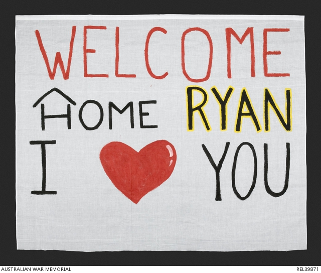 Welcome Home banner made from a cut down white cotton sheet with 'WELCOME / HOME RYAN / I [LOVE] YOU' painted on it. REL39871.