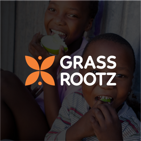 Two kids in smiling and eating fruit with Grassrootz logo overlay