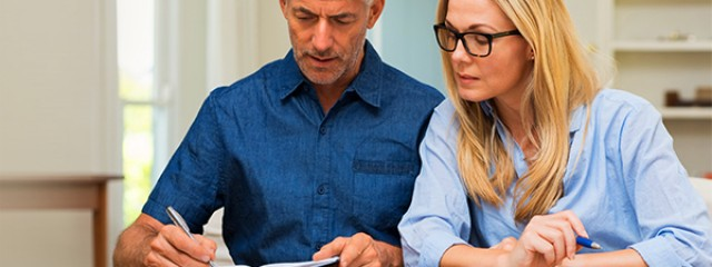 Investor couple writing new financial year resolutions