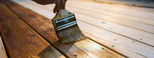 Investor applying varnish to deck