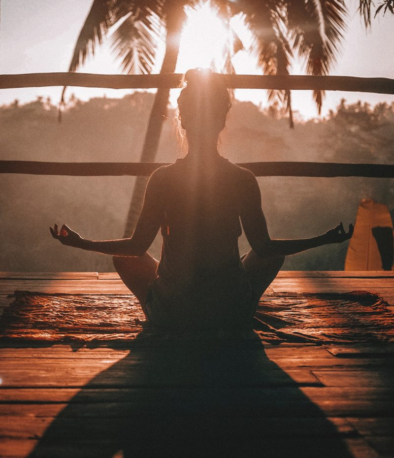 A women does yoga while the sun rises