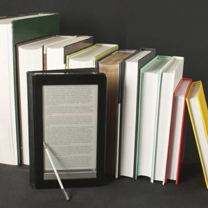 Row of printed books with electronic book reader on black backgr