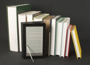 Row of printed books with electronic book reader on black background