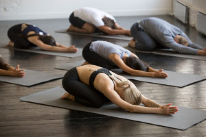 Group of young sporty people in Balasana pose