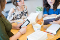 Group of female friends at book club with eBook reader and novels