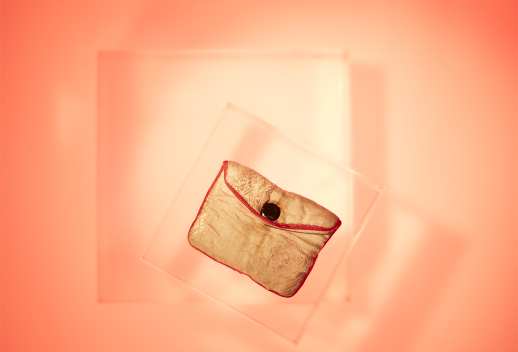Pouch: Pink Silk, Vietnam pre 1978, Small floral pink silk pouch edged with red ribbon and closed with one metal button. Orange lit background, courtesy Immigration Museum, Melbourne