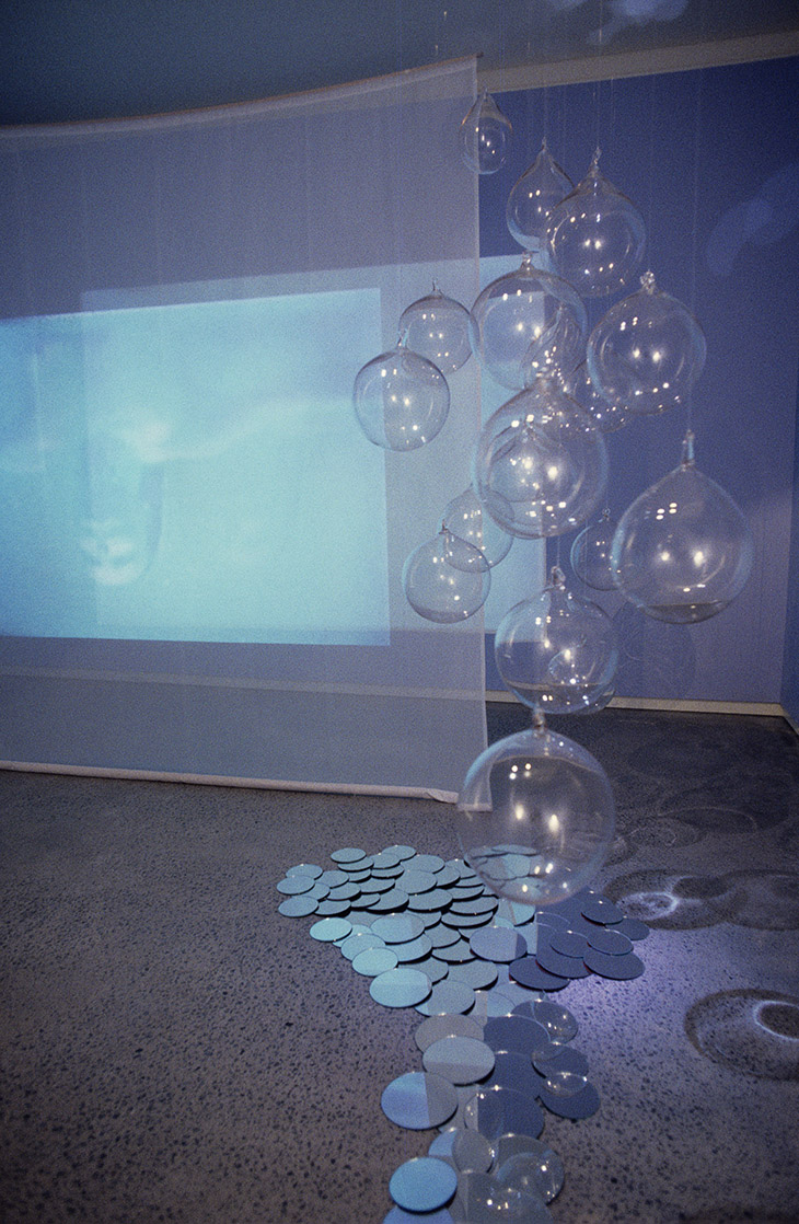 Rosslynd Piggott, Fall 1993–94 (installation detail) video projection, gauze, glass, mirrors, round plinth, milk dimensions variable © The artist Photo: courtesy the artist