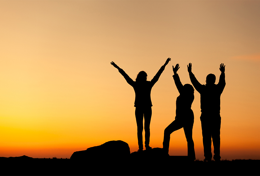 Silhouette of happy family with arms raised up at sunset