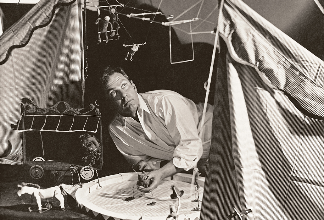 Alexander Calder in his studio, laying on floor looking up at circus sculpture. Detail: (Photo by George Hoyningen-Huene/Condé Nast via Getty Images)