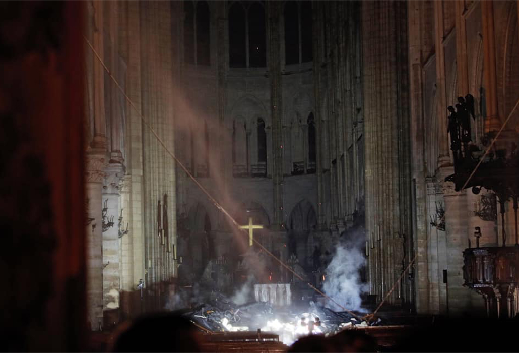 The cross, illuminated among the ruins of Notre Dame Cathedral Paris, following the fire that nearly destroyed this shining icon at the heart of France and its people.