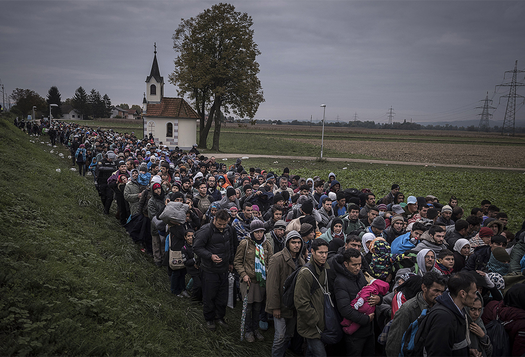 Migrants walk past the temple as they are escorted by Slovenian riot police to the registration camp outside Dobova, Slovenia, Thursday October, 22, 2015. (Photo Sergey Ponomarev for The New York Times)                              NYTCREDIT: Sergey Ponomarev for The New York Times