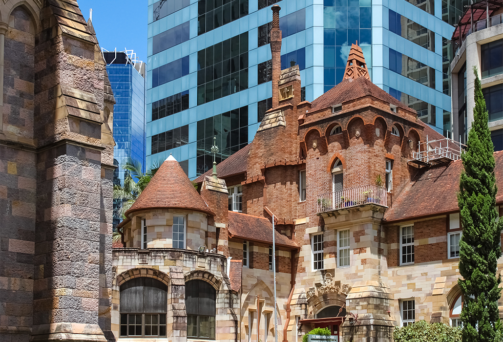 Juxapositon of both old and new buildings - St Martins House, a beautful and ornate former hospital and memorial for veterans stands against contemporary buildings in Brisbane, Australia and next to St John's Cathedral