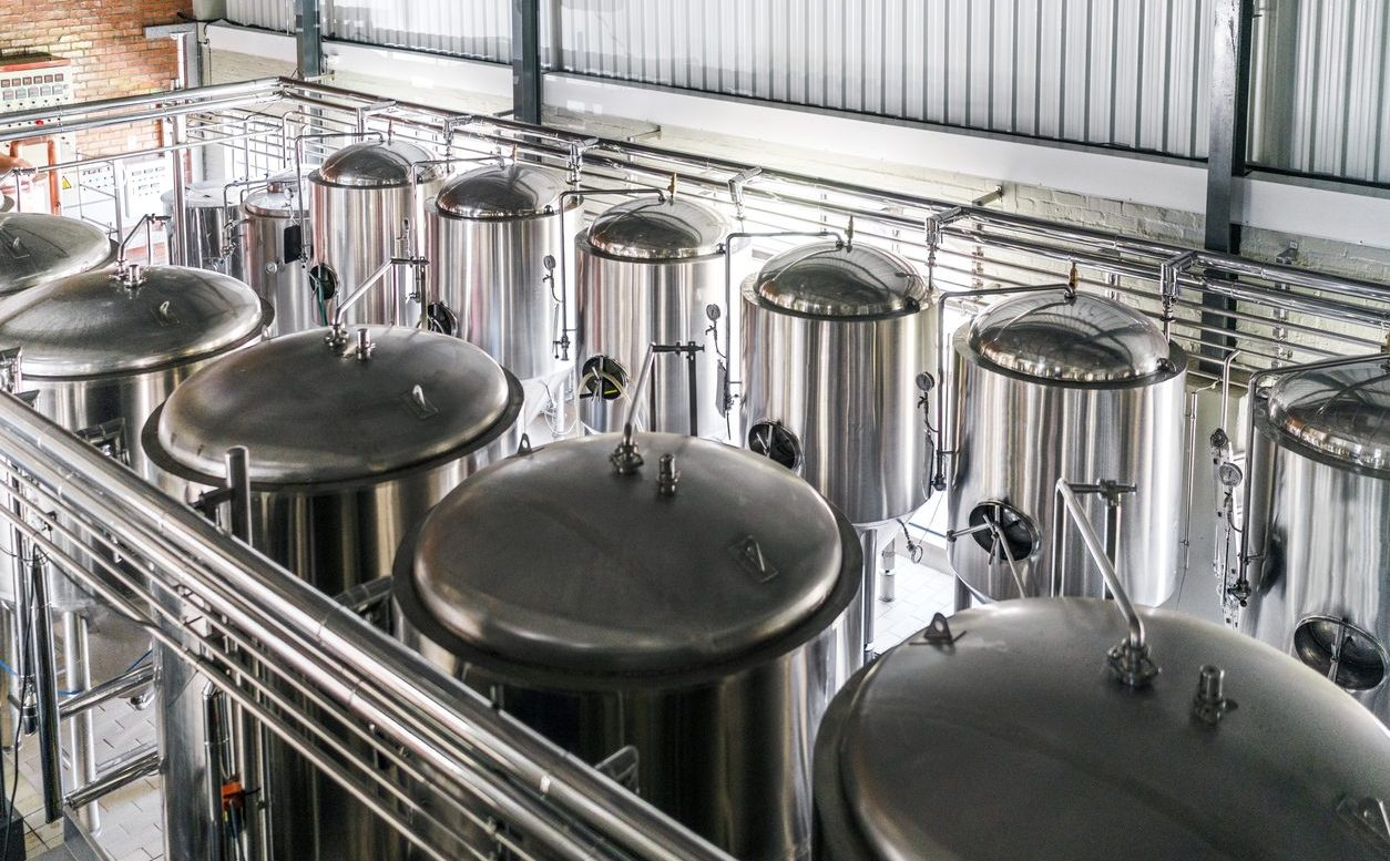 Metallic vats in brewery. High angle view of steel containers in factory. Beer is stored in huge storage tanks at industry.