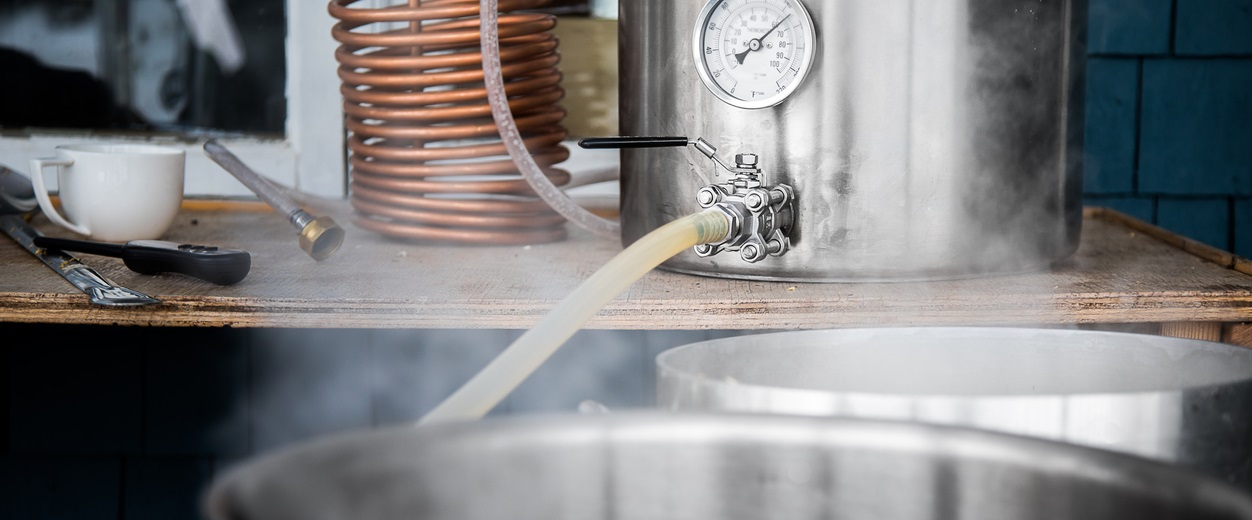 Home Brewing Kit and Pouring Craft Beer Wort into the Boil Kettle with a Silicone Tube.
