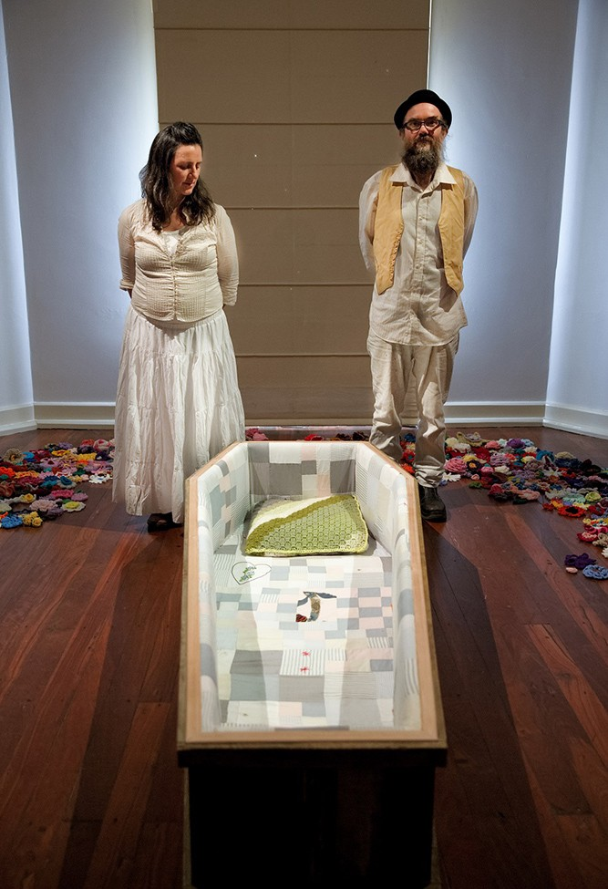 The two artists stand beside the coffin.