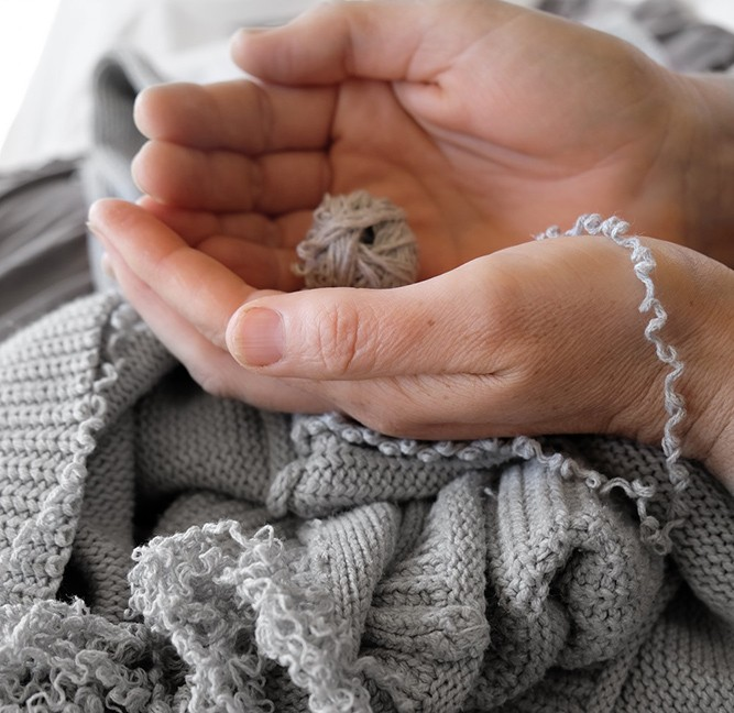 Hands unravelling a knit sweater.