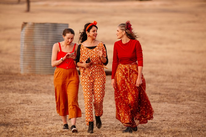 Three women walk towards the camera, smiling as they talk to each other.