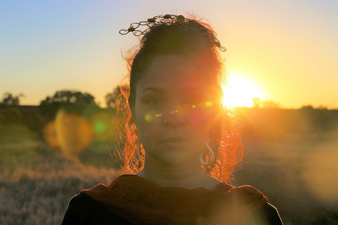 A picture of artist, Yola Baker, with the sun setting behind her. She is in partial silhouette, obscured by glare.