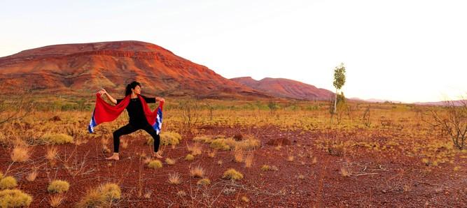 Yola Bakker, strikes a dance pose on the left side of frame, backgrounded by a scene of Australian red desert and rolling hills.