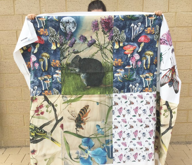 Alicia holds aloft a large piece of clothed, adorned with tea-towel sized recatangular patches each containing asutralian flora and fauna.