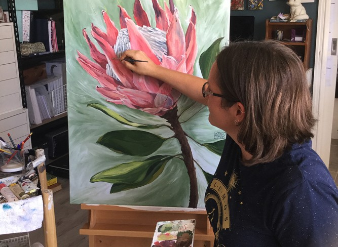 Alicia works on a painting of a large pink flower.