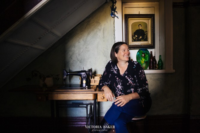 Alicia sits in a chair next to an antique sewing machine in a dimly lit room adorned with green blown glass ornaments. She smiles and looks off to the right side of the frame - at something unseen.