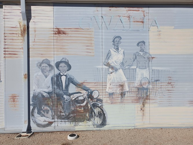 "A mural on a tin wall, depicting a pair of women (dressed in attire which looks dated - perhaps late 60's) preparing for a tennis match and a man on a motorbike (dressed quite formally - including suit, bow tie, and bowler hat) - another man sits on the back of his bike catching a ride. The word ""Gwalia"" can be made out faintly in the background of the mural."