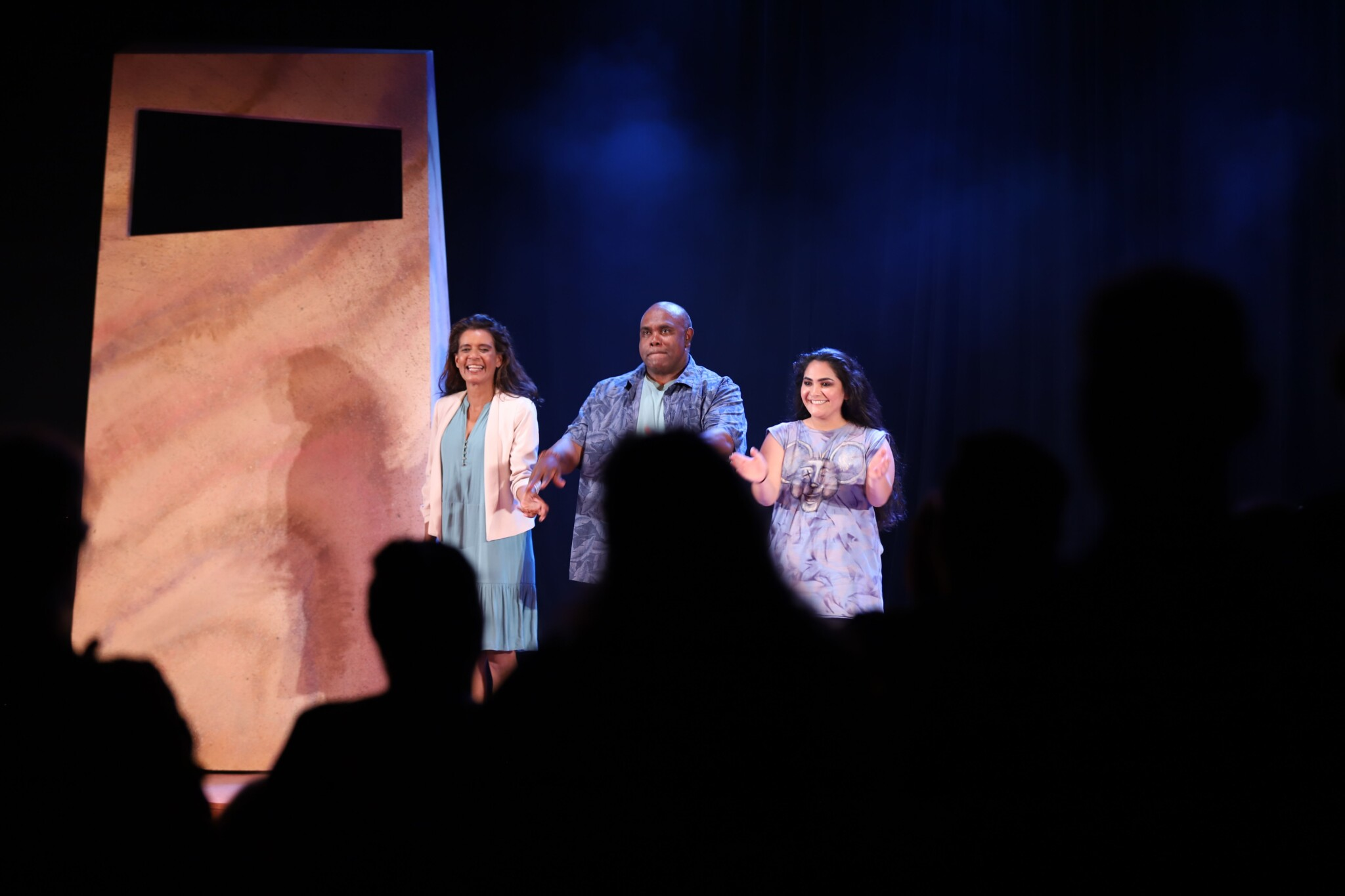 the cast claps on stage as the audience gives a standing ovation