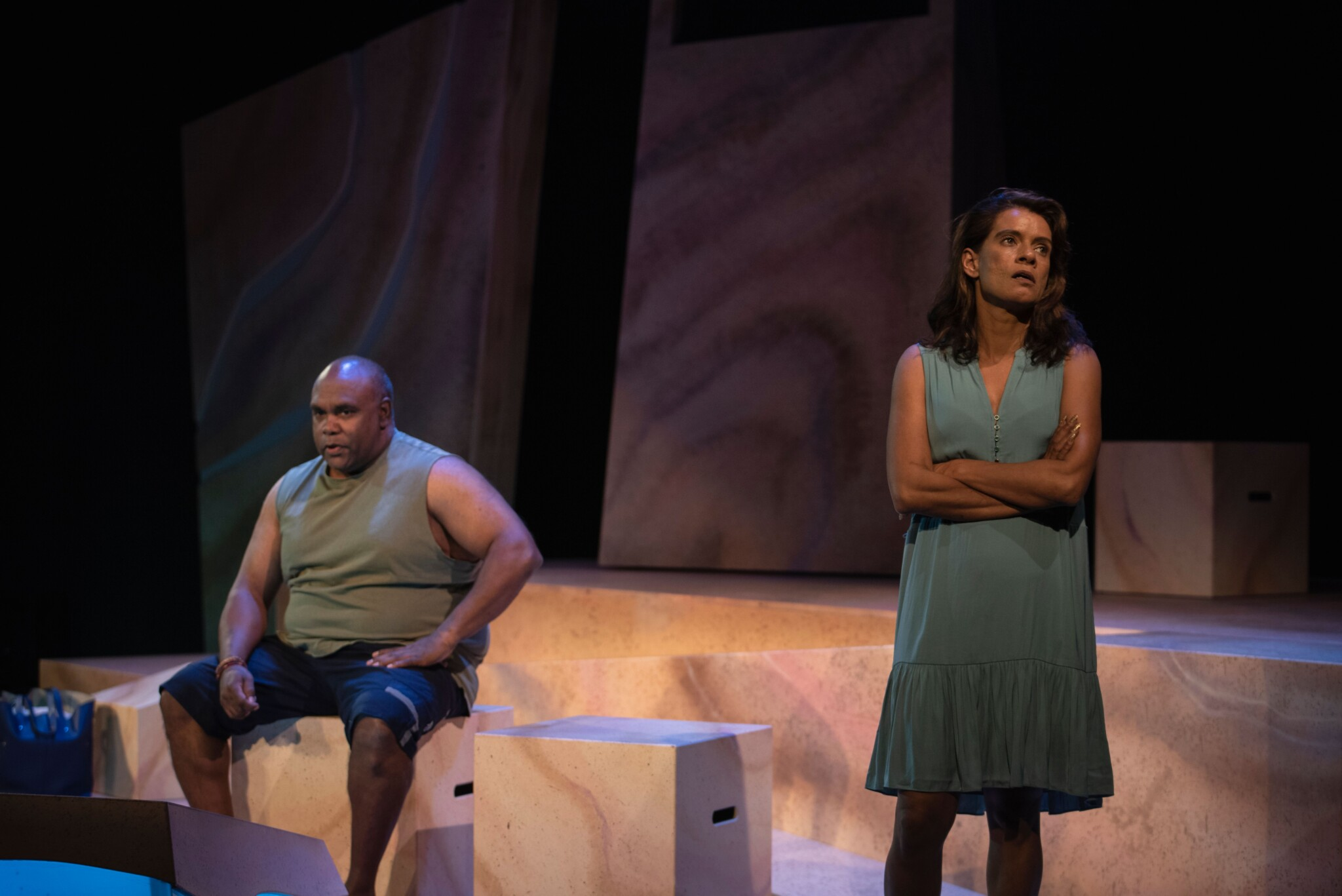 Trevor Ryan sits on the stage, Bobbi Henry has her arms crossed and back to him as if angry