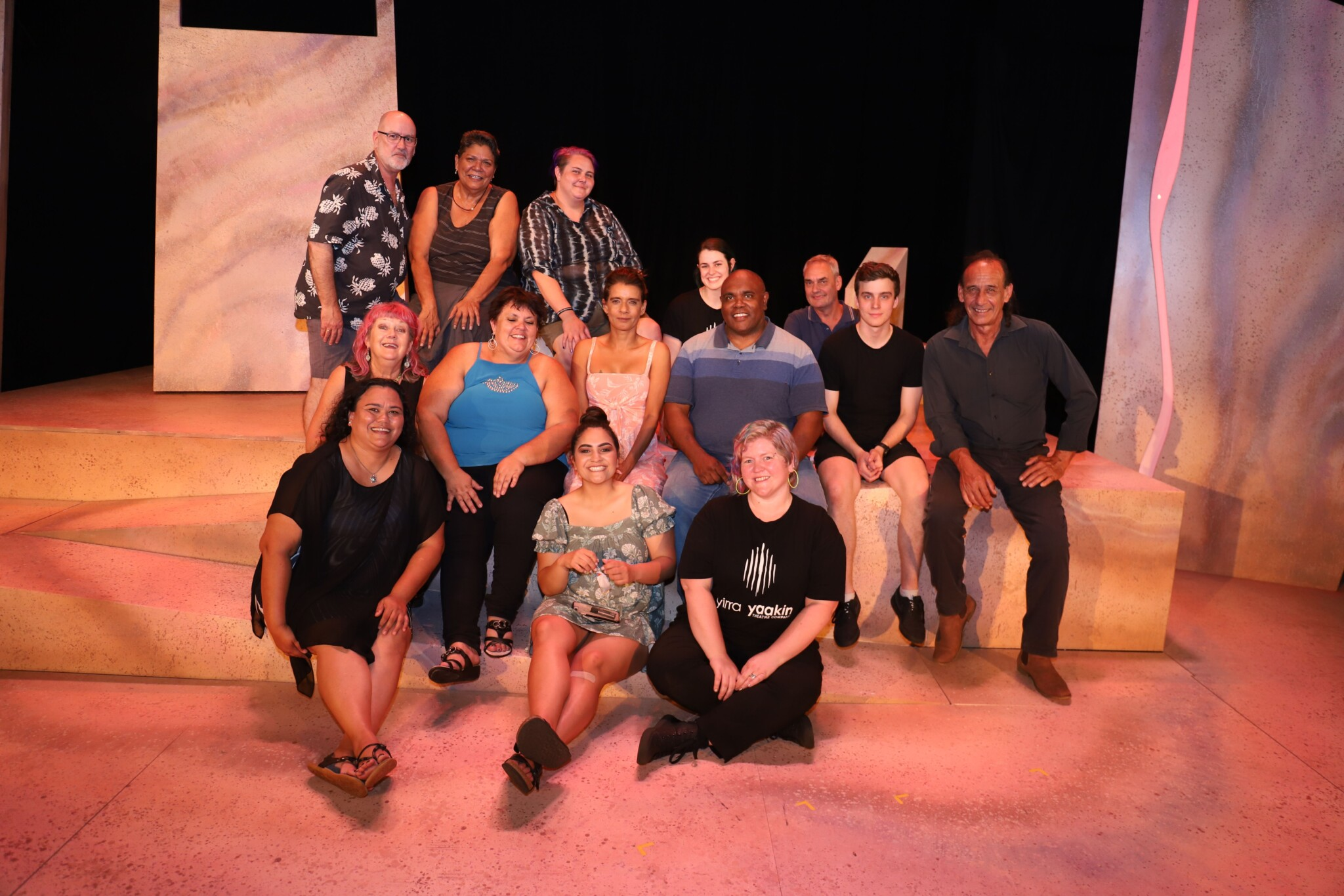 Cast and creative sit and stand on stage as a group