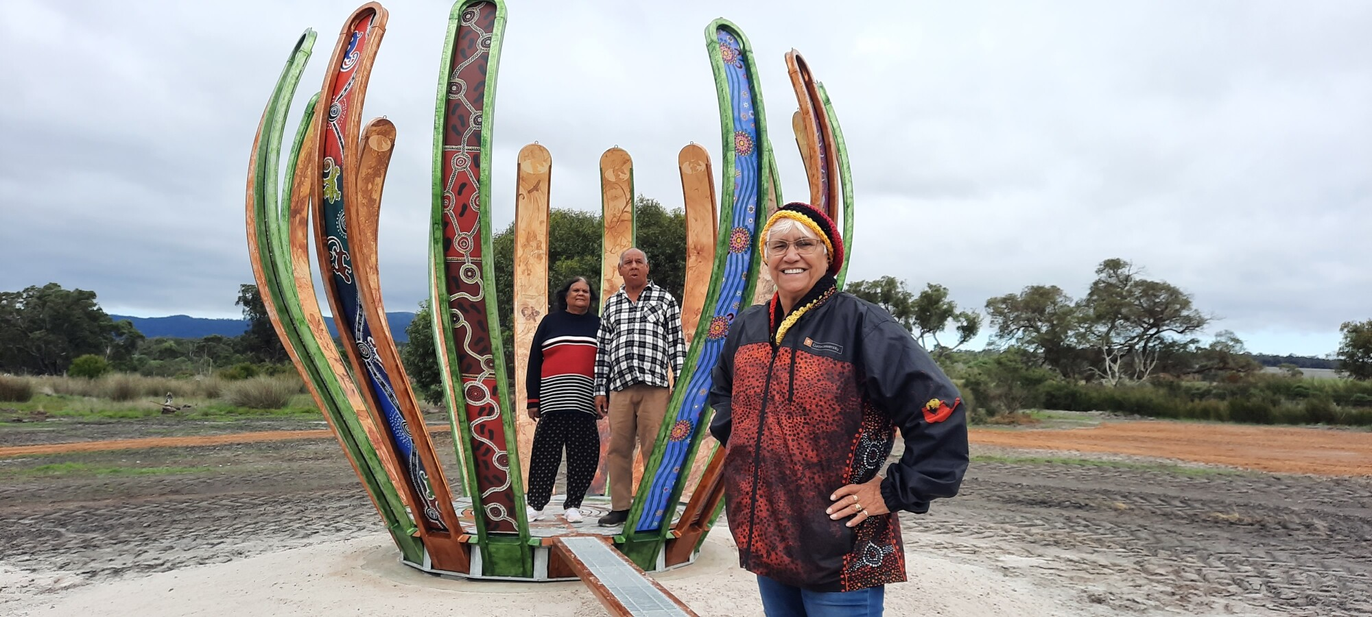 Noongar artist Carol Petterson stands in front of the Genestreams sculpture. Two indigenous workshop participants stand in the middle of the brightly coloured sculpture